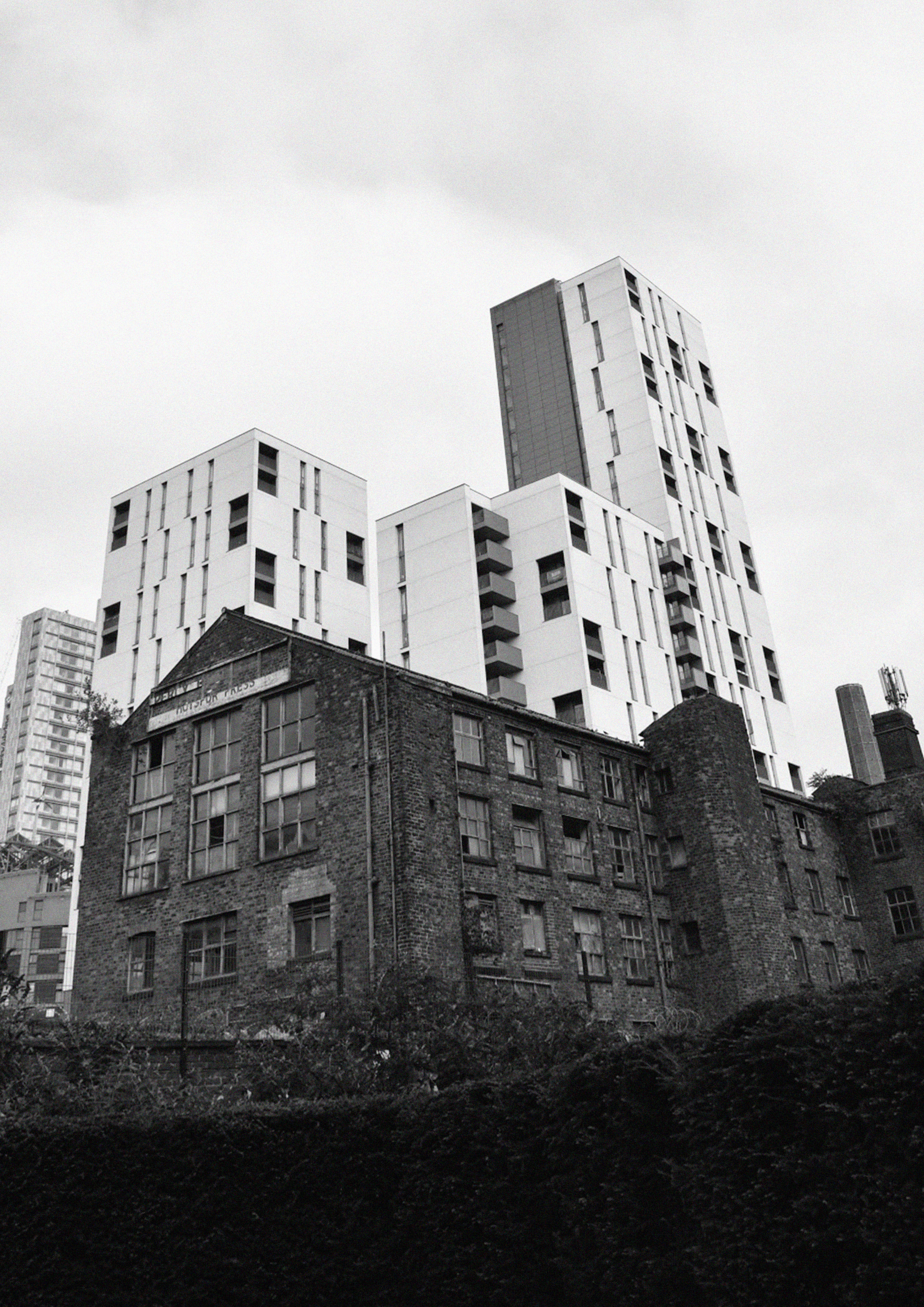 Photograph showing Hotspur Press with tower blocks in the background.
