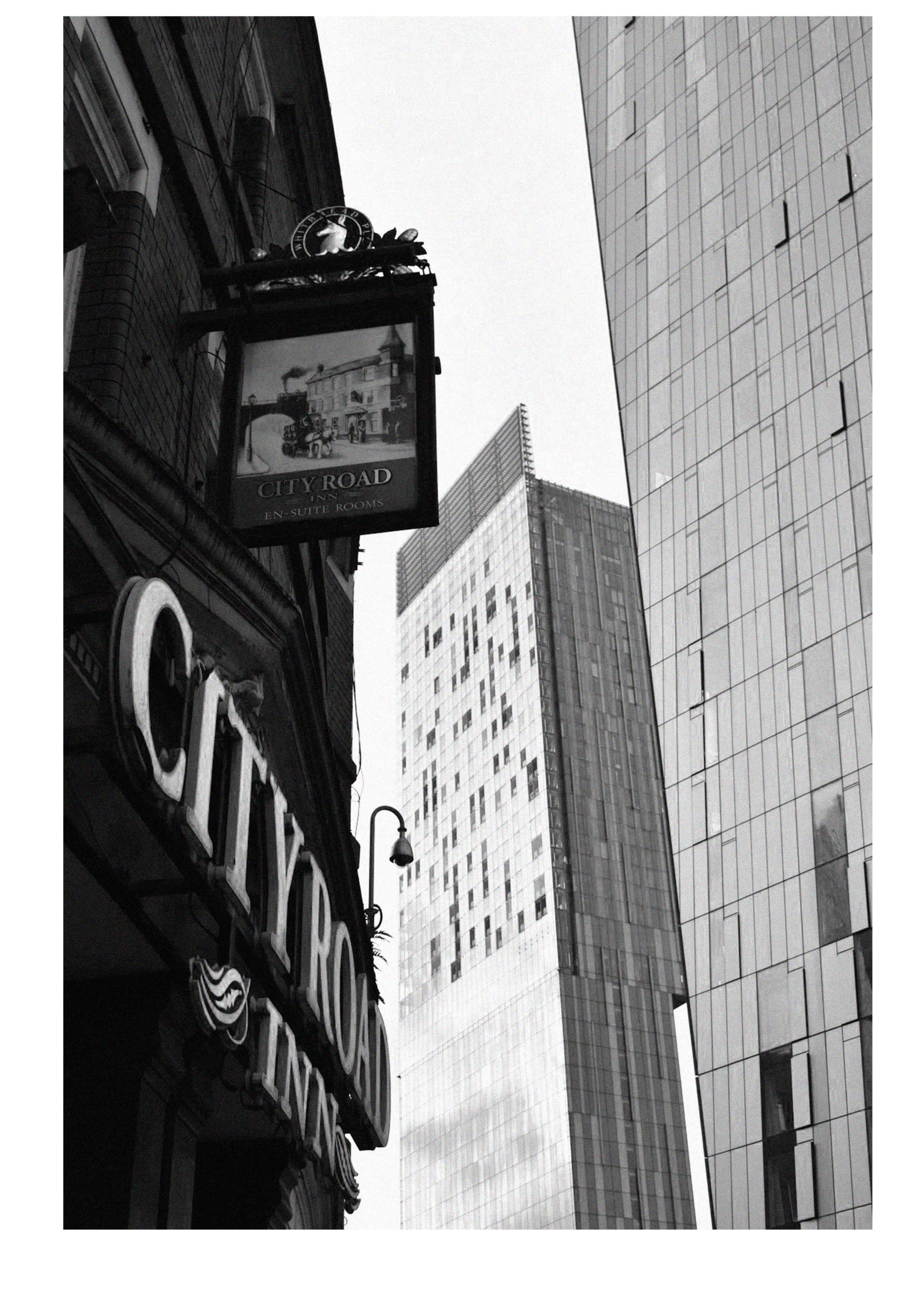 Black and white photography of City Road Inn with skyscrapers in the background. Manctopia.